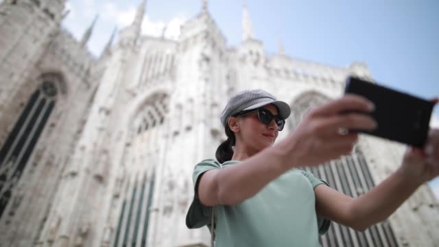 woman taking selfie in front of milano cathedral - courtyard stock videos & royalty-free footage