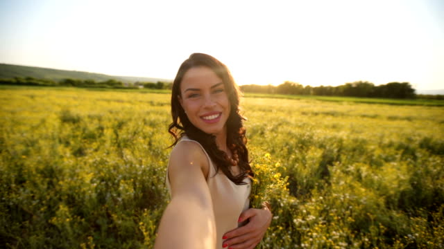 woman taking selfie in nature at sunset - selfie video stock e b–roll