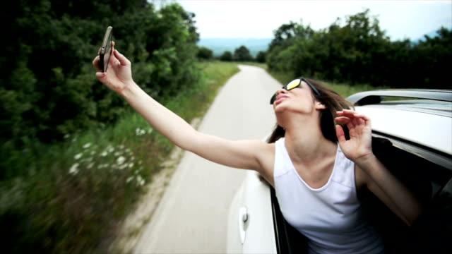 vidéos et rushes de femme prenant un selfie dans la voiture. ralenti - lunettes de soleil