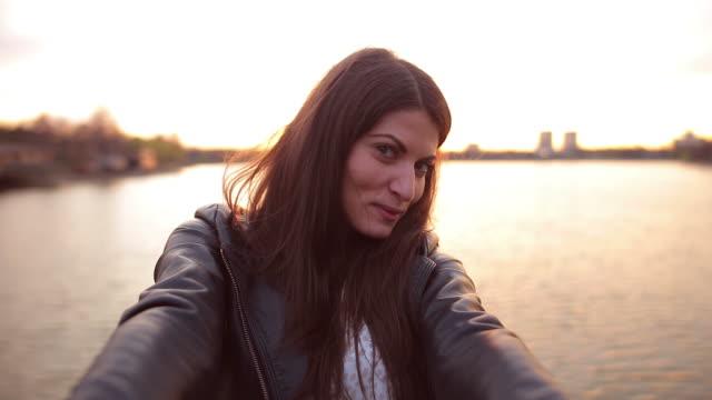 vídeos y material grabado en eventos de stock de mujer tomando autofoto en el parque. - mujeres de mediana edad