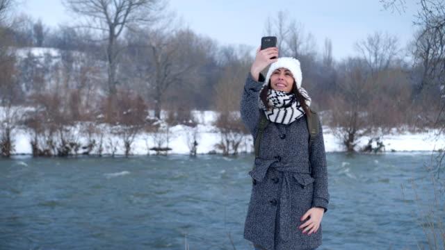 Woman taking selfie near the river