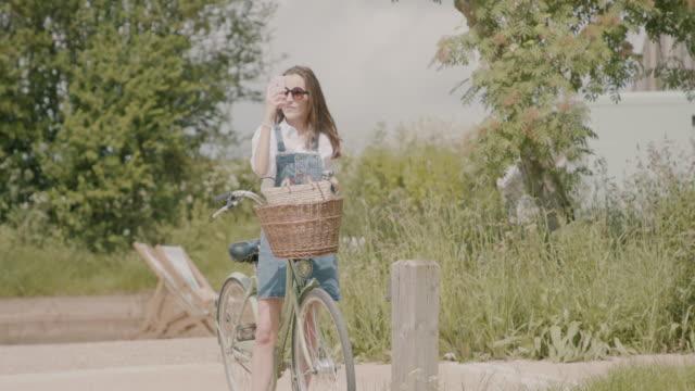vídeos de stock e filmes b-roll de woman taking selfie on bicycle outside - chipping norton england