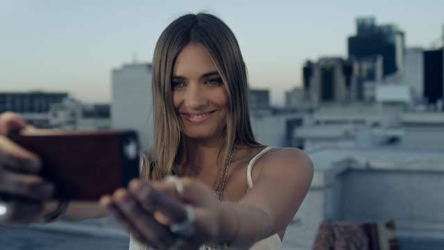 stockvideo's en b-roll-footage met woman taking selfie on rooftop - fotoberichten