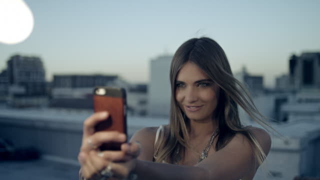 donna prendendo selfie sul tetto - selfie video stock e b–roll