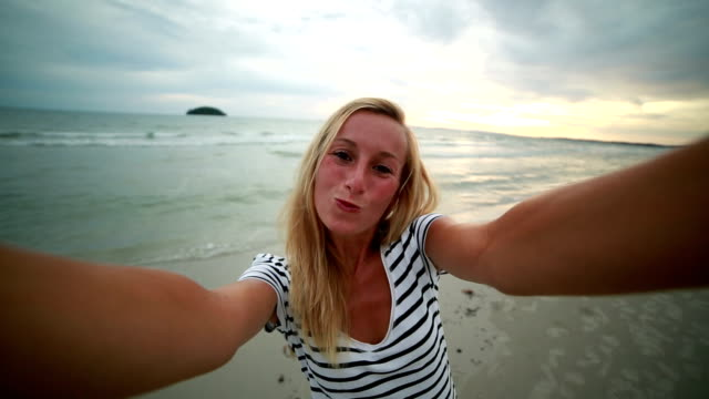 Woman taking selfie on the beach at sunset