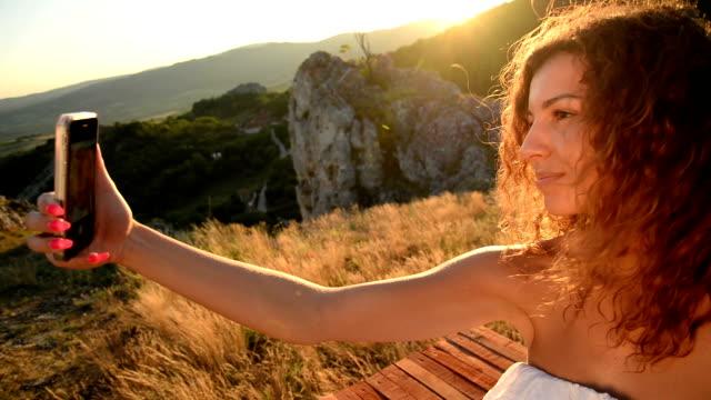 セルフィーを取る女性 - landscape scenery点の映像素材/bロール