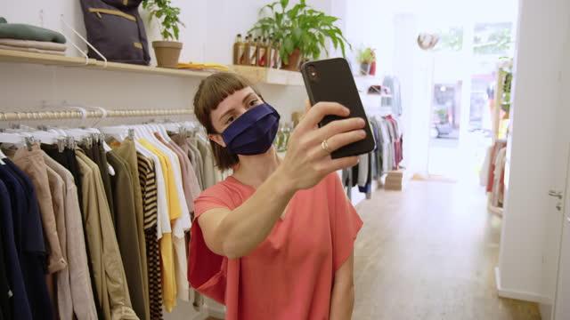 frau macht selfie beim einkaufen in boutique - new stock-videos und b-roll-filmmaterial