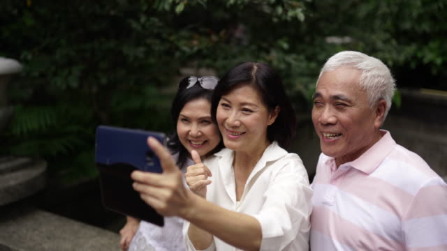 woman taking selfie with her senior friends - chinese ethnicity stock videos & royalty-free footage