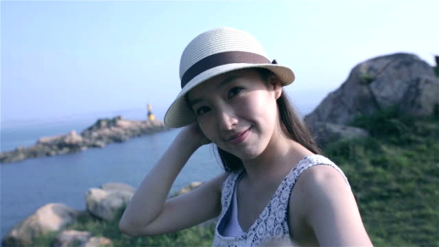 Woman taking selfie with ocean background