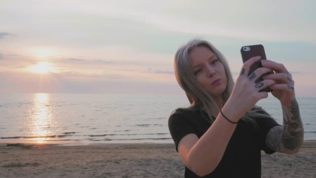 Woman taking selfies at the beach in Sweden during sunset