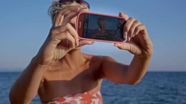 vídeos de stock, filmes e b-roll de ms mulher tirar autorretratos na praia - raw footage