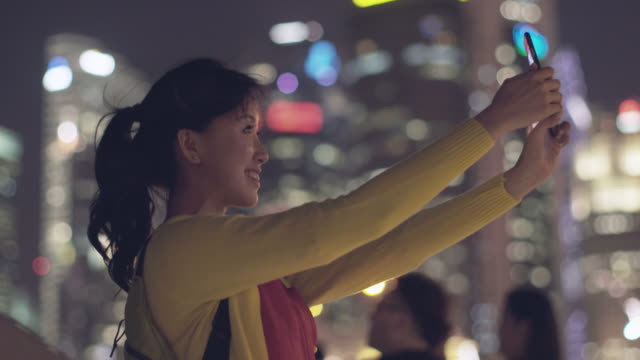 MS Woman taking smartphone selfie in modern city