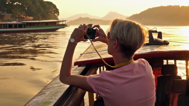 woman taking sunset photograph with camera on mekong river cruise - tourist stock videos & royalty-free footage