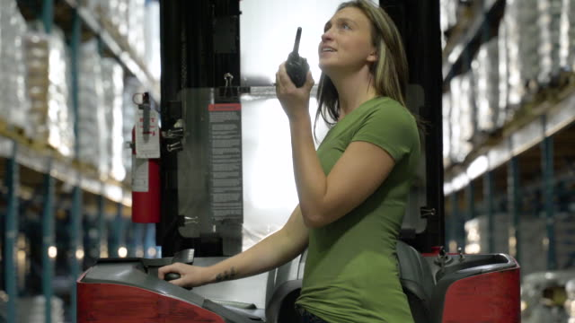 woman talking into hand held radio system in aisle of warehouse, forklift machinery in background - pacific islander background stock videos & royalty-free footage