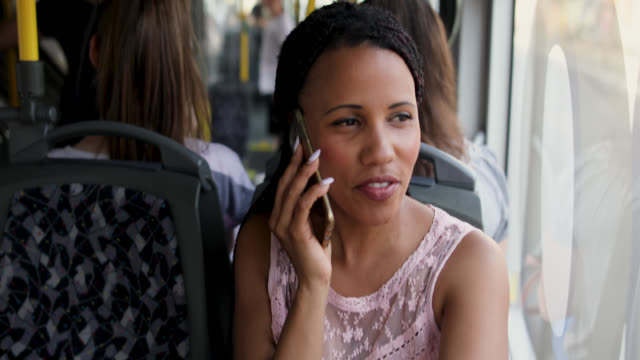 woman talking on a phone while traveling by a bus - public transportation stock videos & royalty-free footage