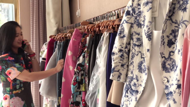 stockvideo's en b-roll-footage met woman talking on cell phone and shopping in clothing store - kledingrek