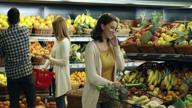 vídeos y material grabado en eventos de stock de mujer hablando por teléfono celular y comerciales - supermercado