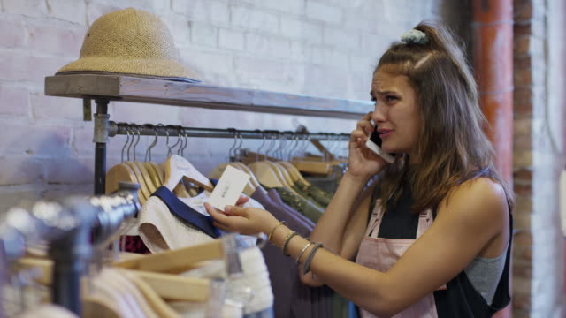 Woman talking on cell phone in clothing store frustrated then happy / Provo, Utah, United States