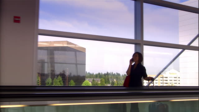Woman talking on cell phone while riding moving sidewalk at SeaTac Airport / Washington State