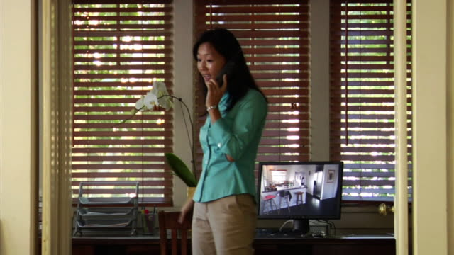 ms woman talking on cordless phone while pacing in front of computer / los angeles, california, usa - cordless phone stock videos & royalty-free footage