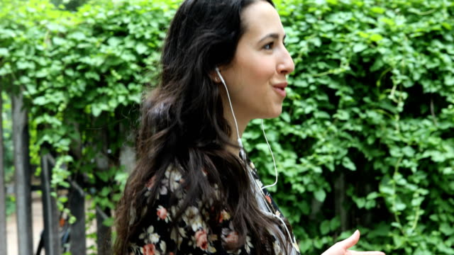 woman talking on earphones using phone by plants - fence stock videos & royalty-free footage