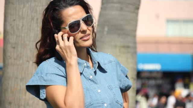 woman talking on her cellphone - korta ärmar bildbanksvideor och videomaterial från bakom kulisserna