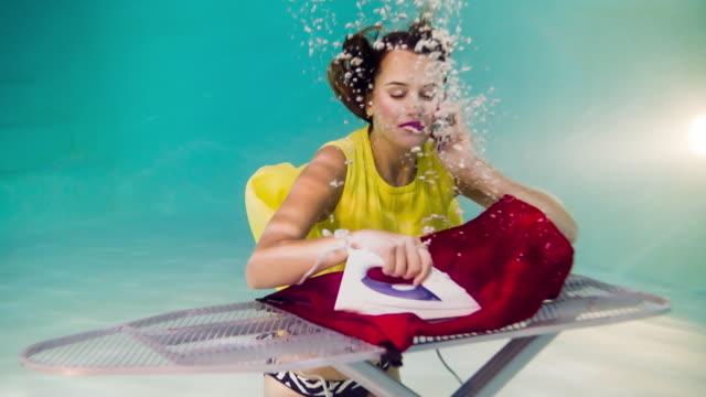 Frau am Handy und ein Bügeleisen/-Brett unter Wasser