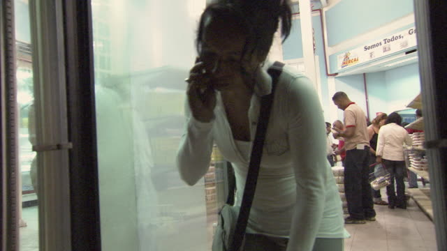 MS TD Woman talking on mobile phone picking meat from refrigerator at Mission Mercal store / Cabimas, Zulia, Venezuela