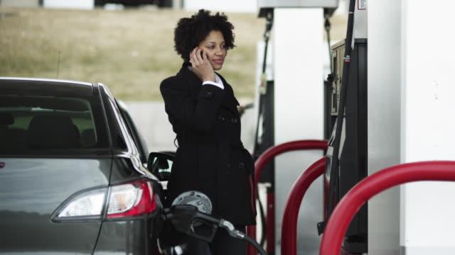 MS Woman talking on phone at gas station / Orem, Utah, USA