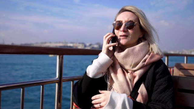 海で電話で話している女性 - 受話器点の映像素材/bロール