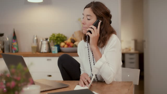 woman talking on phone in front of laptop at home - wohngebäude stock-videos und b-roll-filmmaterial