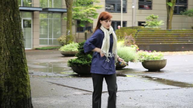 WS PAN Woman talking on phone while walking through urban park / Portland, Oregon, USA
