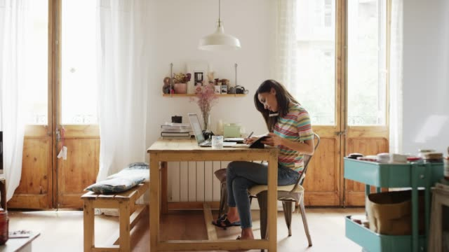 woman talking on smart phone while working at home - dolly shot stock videos & royalty-free footage