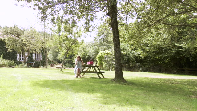 ws woman talking on smartphone and drinking coffee at picnic table in garden in front of house / saint junien, central france, france - picnic table stock videos and b-roll footage