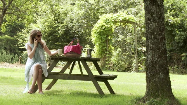 MS Woman talking on smartphone and drinking coffee at picnic table in garden / Saint Junien, Central France, France