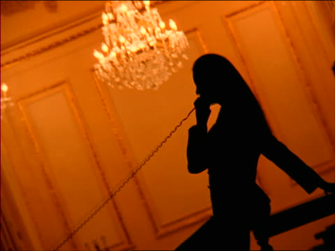 orange canted silhouette woman talking on telephone + laughing / chandelier in background - 1998 stock-videos und b-roll-filmmaterial