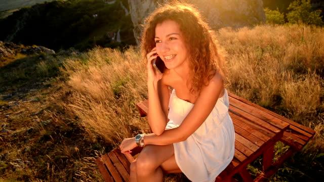 donna parlando sul telefono e guardando alla macchina fotografica - gambe accavallate video stock e b–roll