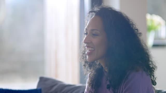 frau auf dem sofa reden und lachen - mittellanges haar stock-videos und b-roll-filmmaterial