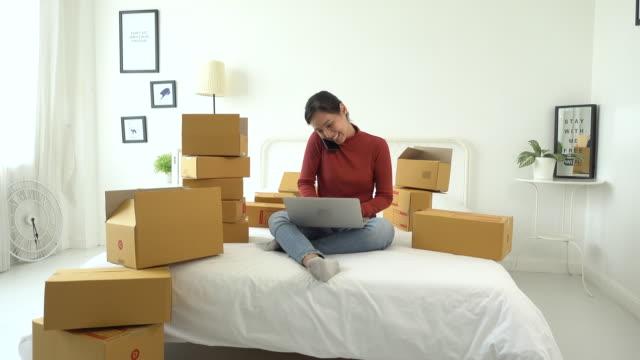 kvinna pratar telefon med sin kund för sälj online hemma, paket låda hemma kontor - sälja bildbanksvideor och videomaterial från bakom kulisserna