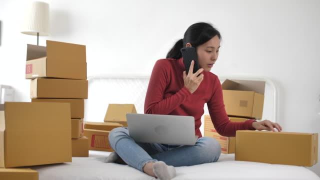 自宅でオンライン販売のための彼女の顧客と電話を話す女性、ホームオフィスの小包ボックス - 段ボール箱点の映像素材/bロール