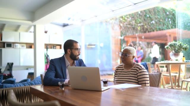 vídeos de stock e filmes b-roll de woman talking to finance advisor at home - acaso