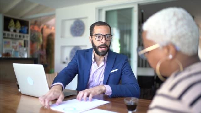 vídeos de stock, filmes e b-roll de mulher falando com consultor financeiro em casa - perícia