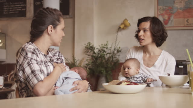 vídeos de stock, filmes e b-roll de woman talking to friend while breastfeeding baby - breastfeeding