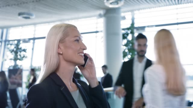 ds woman talking to her family on the phone while walking through the business lounge at the airport - contented emotion stock videos & royalty-free footage