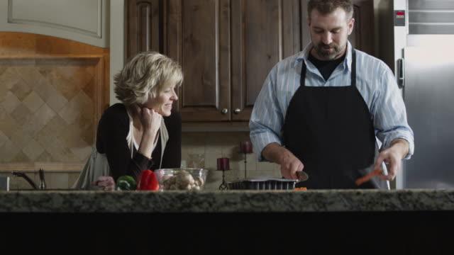 ms tu woman talking to man cutting carrot in kitchen / orem, utah, usa - orem bildbanksvideor och videomaterial från bakom kulisserna