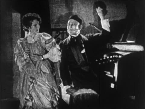 b/w 1925 woman (mary philbin) talking to organist with mask on face (lon chaney) / feature - anno 1925 video stock e b–roll