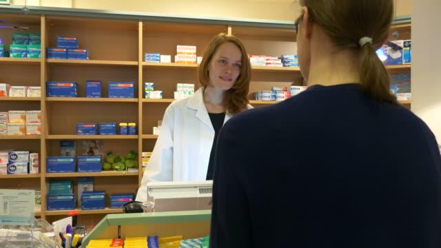 Vrouw in gesprek met de apotheker In winkel