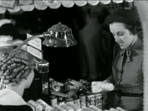 b/w 1938 woman talking to saleswoman + paying at counter in 5 and 10 store / industrial - till stock videos & royalty-free footage