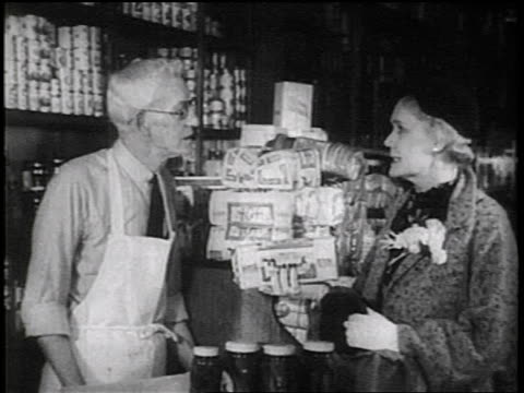 b/w 1936 woman talking to senior grocer at counter while holding loaf of bread / documentary - bread stock videos & royalty-free footage