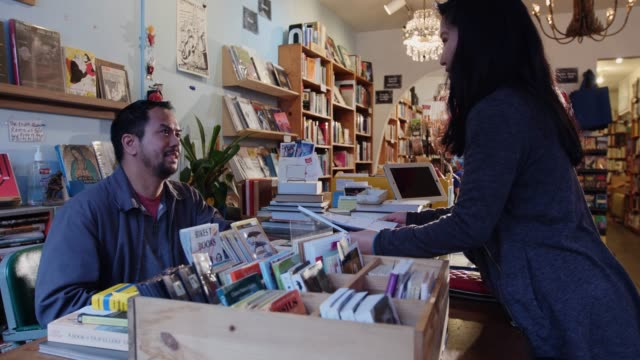 woman talking with bookstore owner - book shop stock videos & royalty-free footage